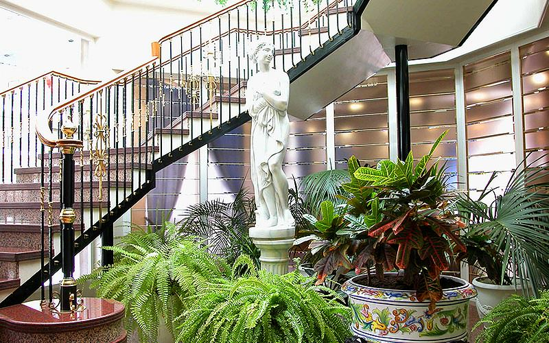 A staircase in the back, with plants and a white statue in the foreground