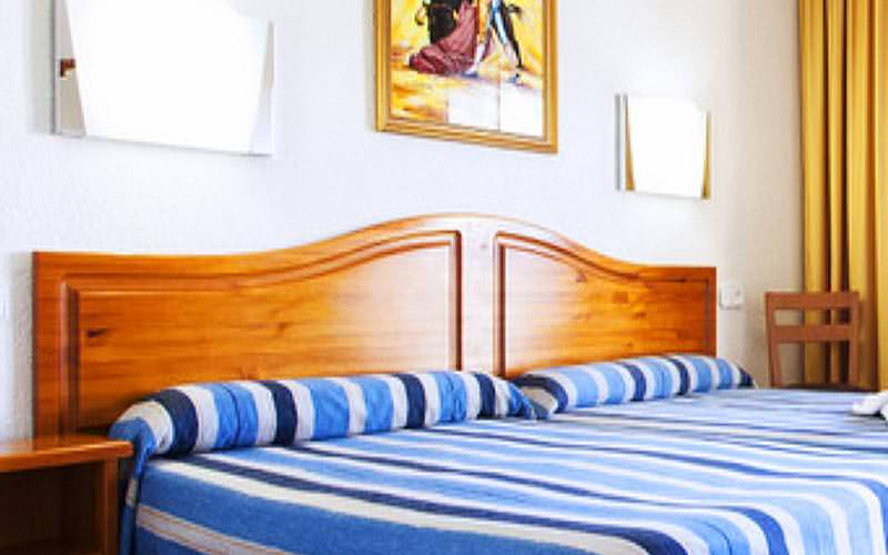 Two double beds with blue and white striped bedding, with a bedside table in the corner
