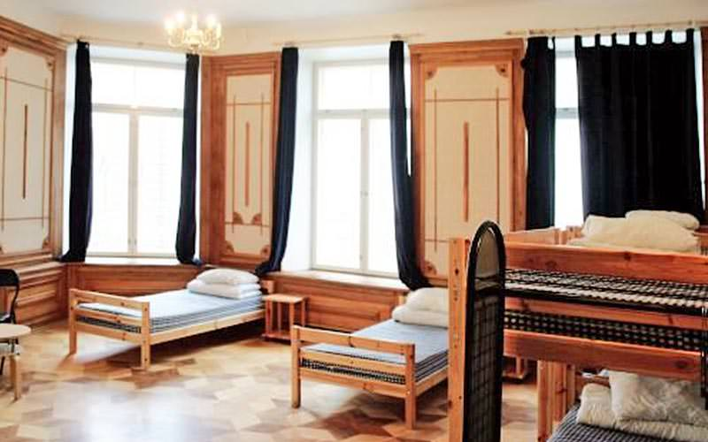 A large wooden panelled room with wooden framed twin and bunk beds