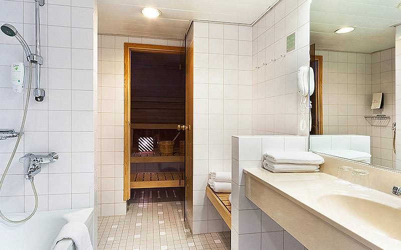 A white tiled bathroom with a sauna