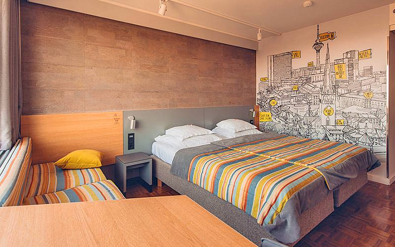 A twin guest room with striped bed covers and a mural map on the wall