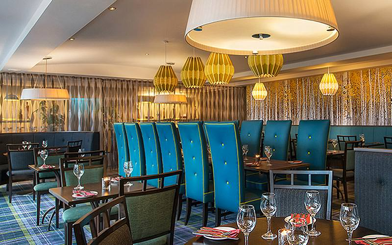 High blue chairs around a long table set for dinner, with various other tables around, in the hotel restaurant at Jurys Inn Galway