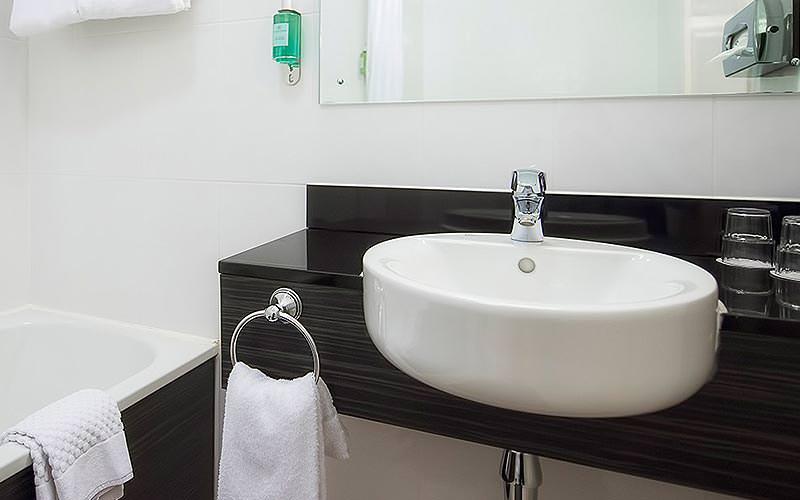 A white sink on a black bathroom counter, with a bath in the corner