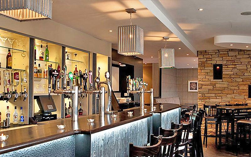 The bar in Jurys Inn Cork, with exposed brick walls and a silver bar