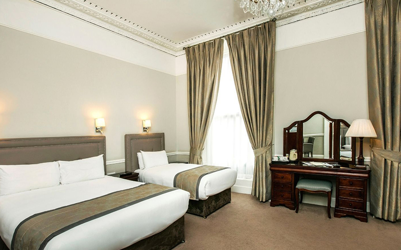 A guest room with two twin beds at the Harcourt Hotel