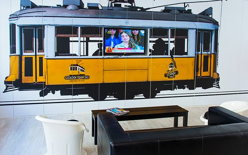 A yellow tram mural on a wall with a TV on top, and a black sofa, white chairs and a coffee table in the foreground