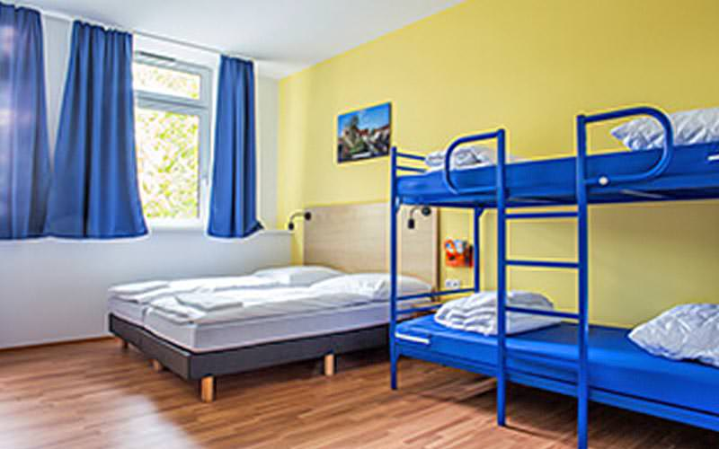 A large guest room with two twin beds and a blue bunk bed