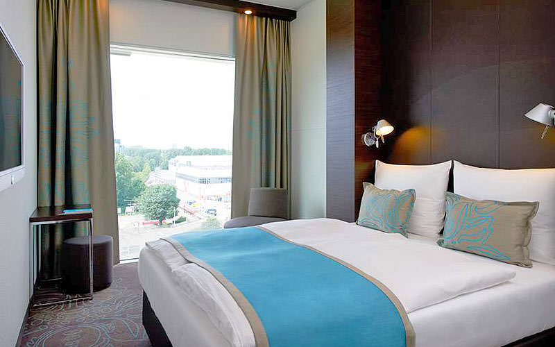 A double room with a blue throw over the bed, and a large window with nice view in the background