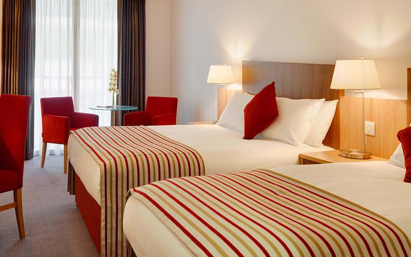 A guest room at the Clayton Hotel Cardiff Lane with two double beds