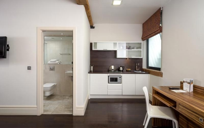 A kitchen area with a view of a bathroom