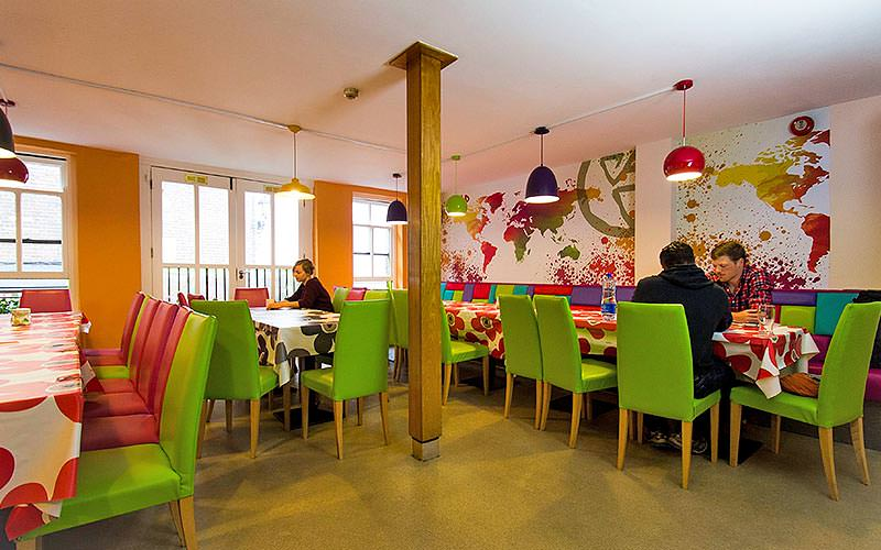 A large communal dining area with brightly coloured chairs and map murals on the walls