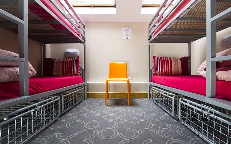 Two bunk beds with red bedding and a yellow chair in between