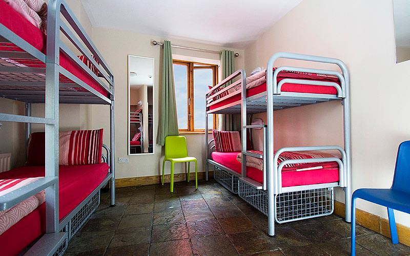 Two bunk beds with red bedding and a green chair in between