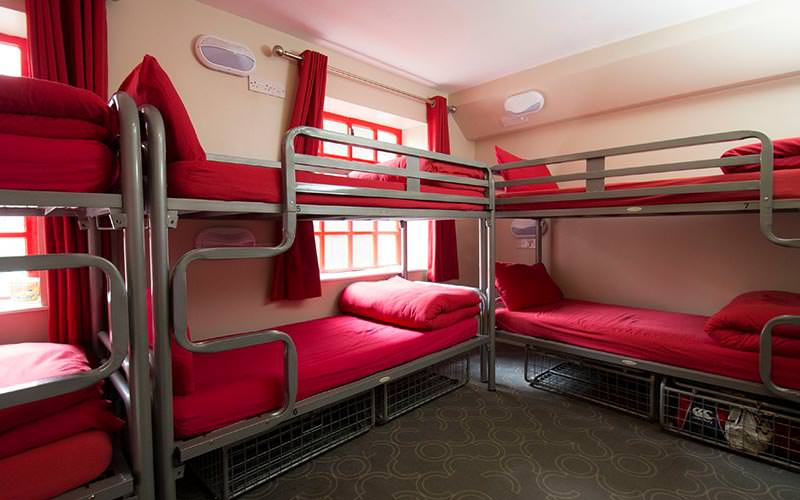 Multiple bunk beds with red bedding