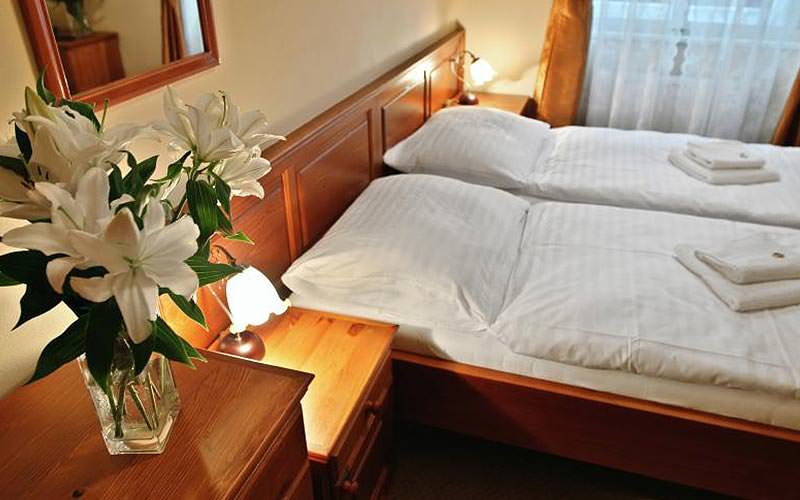 Two white single beds in a hotel room, with a bedside table with flowers on top