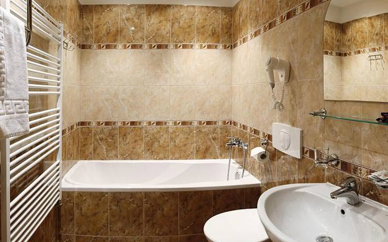 Tiled bathroom with a bath, sink and toilet, as well as a hairdryer on the wall