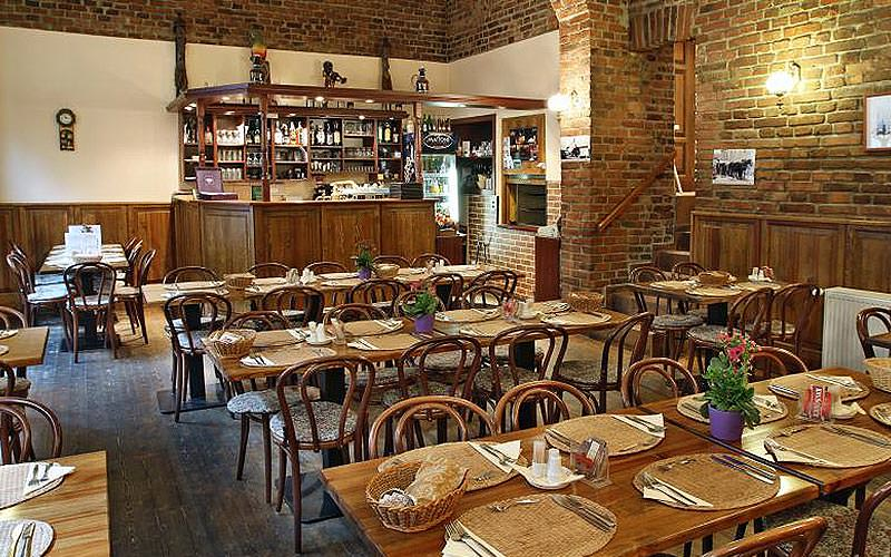 Tables and restaurants set up for dinner in the Achat Restaurant, featuring exposed brick