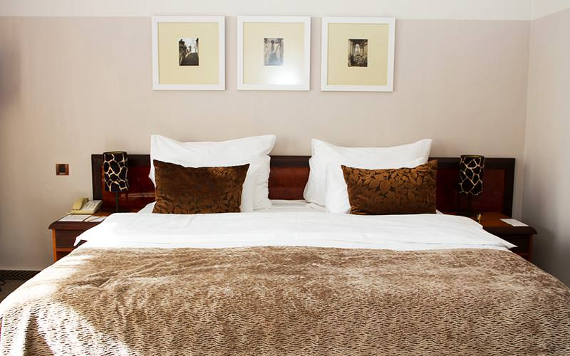 Close up of a white double bed, with three pictures above, topped with a brown throw and two brown cushions
