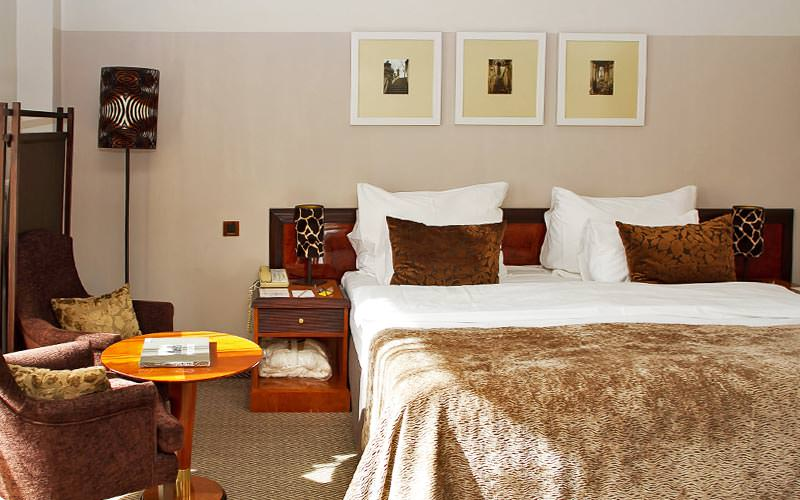 A double bed topped with a brown throw and two brown cushions, with two chairs and a table in the corner of the room