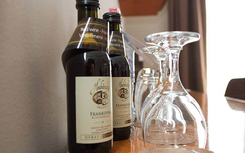 Two wine glasses and two small bottles of wine on a table