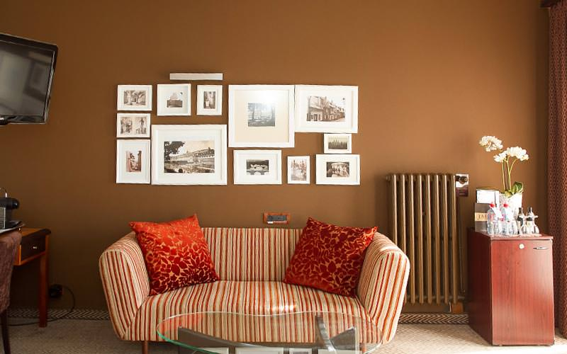 Pictures on a brown wall above a striped sofa, with a desk and TV in one croner, and a table topped with drinks and flowers in the other