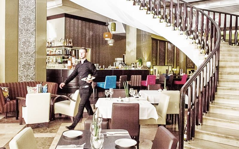 A bartender walking through the empty restaurant at Jalta Boutique Hotel, with a sweeping staircase in the corner