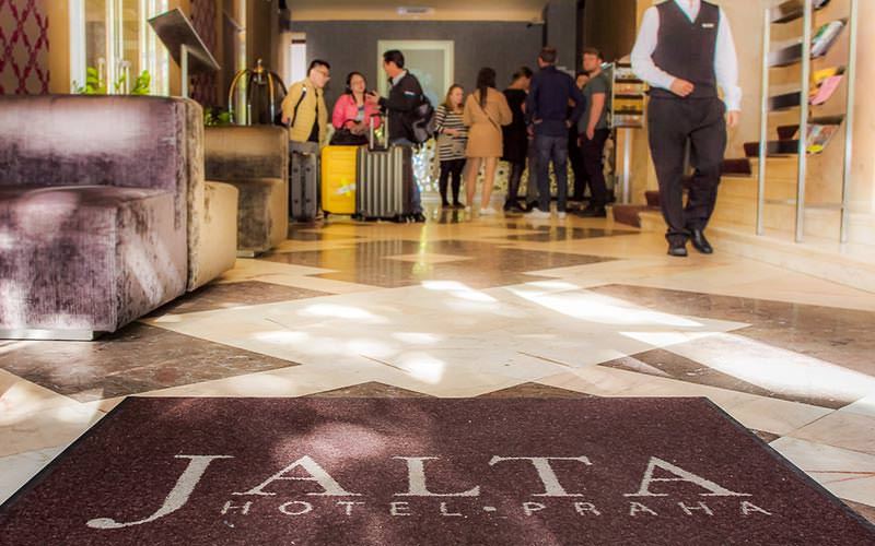 People in the lobby at Jalta Boutique Hotel, with the hotel mat in the foreground