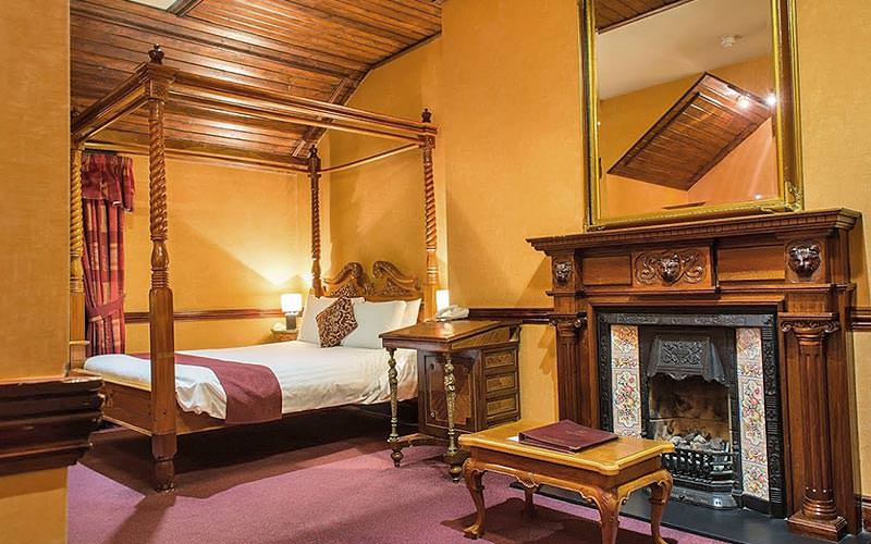 An ornate guest room with an open fireplace and a four-poster bed