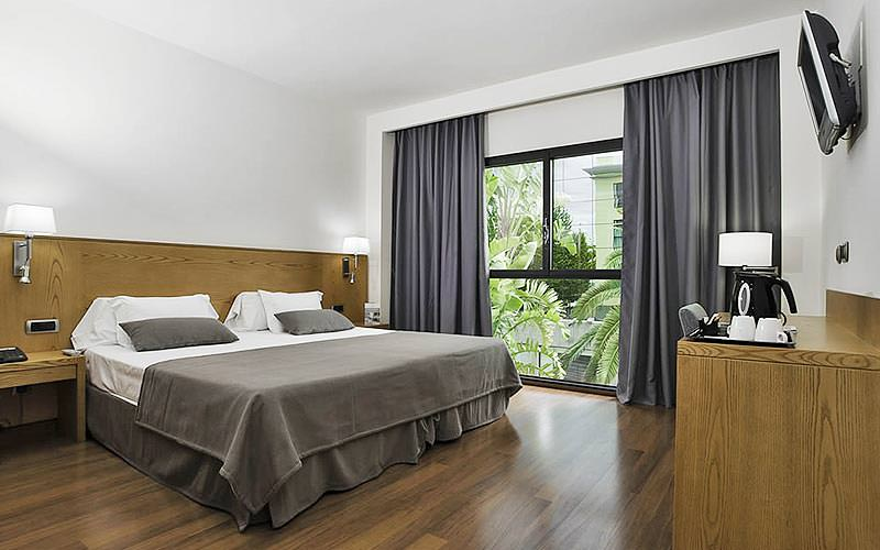 A double room within a modern looking hotel, with the view looking out over some trees