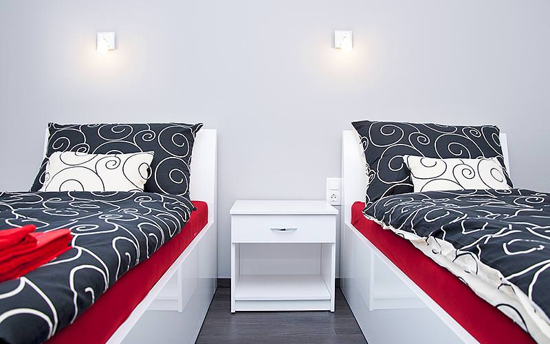 Two single beds up against the wall with a white table in the middle
