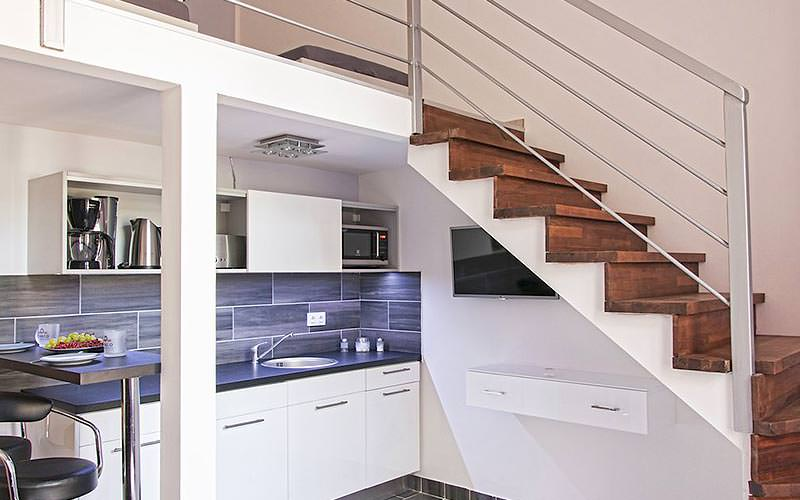 A kitchen area in the apartments with a staircase going up to the top floor