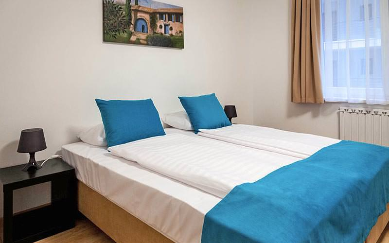A double bed with blue runner and matching cushions on