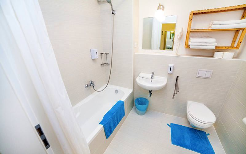 A bathroom with blue towel on the floor and on the side of the bath
