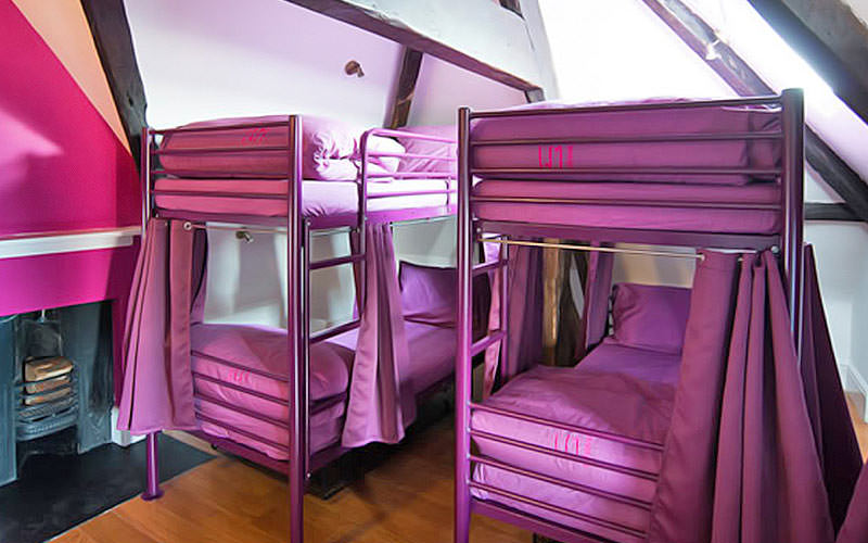 Two bunk beds with purple bedding and exposed beams on the ceiling