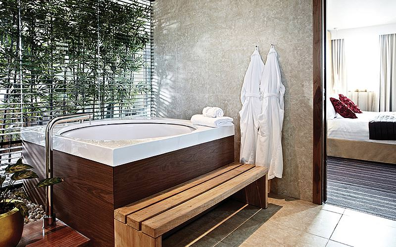 A large Jacuzzi-style bath in a hotel room, with two white robes hung up, a step to the bath and plants in the room