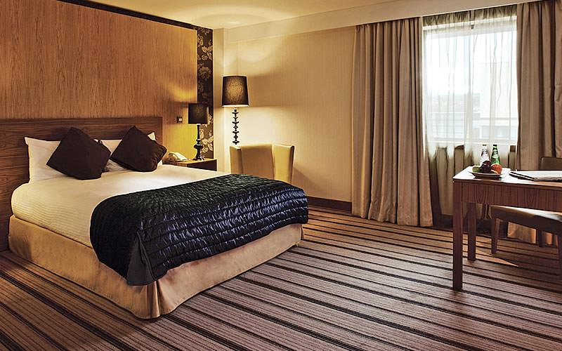 A double bed in a hotel room, with a black throw and brown cushions, facing a desk with fruit on top, and a chair