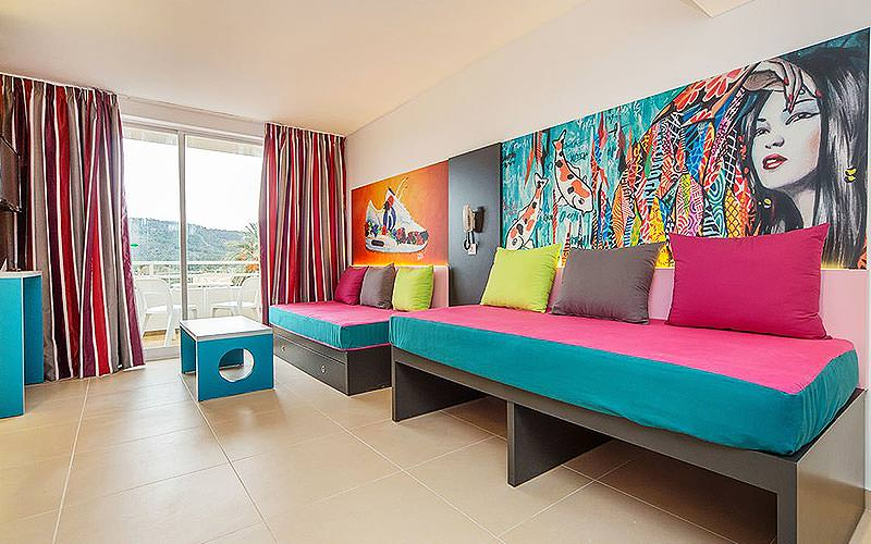 Colourful sofa beds in front of murals on the wall