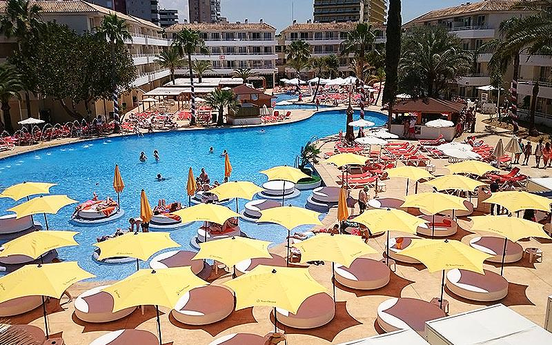 Circular sun beds under yellow parasols, around an outdoor pool