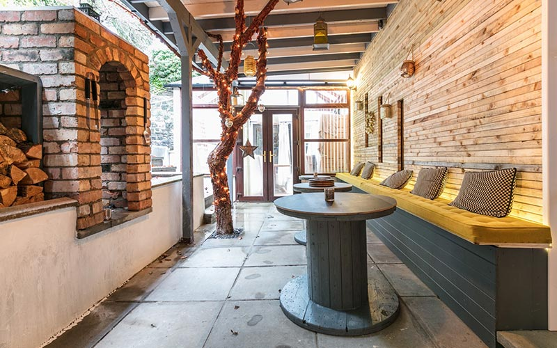 An outdoor terrace with plush seating against the exposed brick wall and a built in fireplace on the other side
