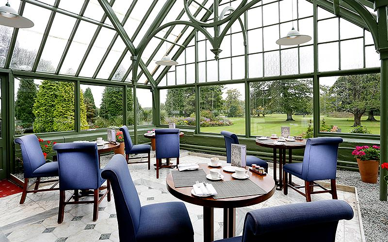 A conservatory with high ceilings and purple seats with tables