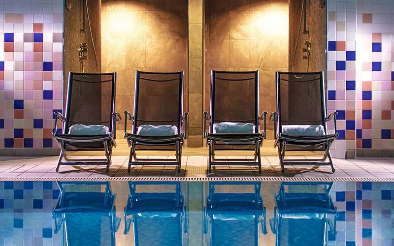 Four deck chairs by an indoor swimming pool