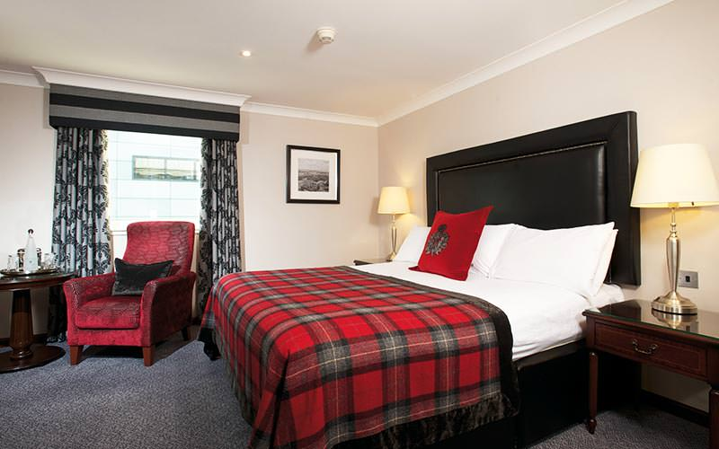 A double bed within Holyrood Hotel, with tartan bedding and a comfortable armchair