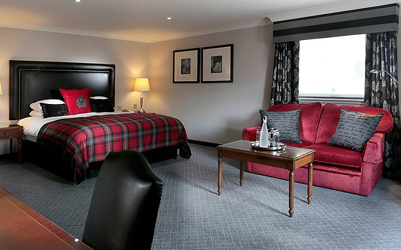 A large room with a double bed which has tartan bedding, and a red sofa with champagne chilling in front of it