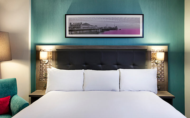 A white double bed in a blue hotel room, with a picture hanging above the bed