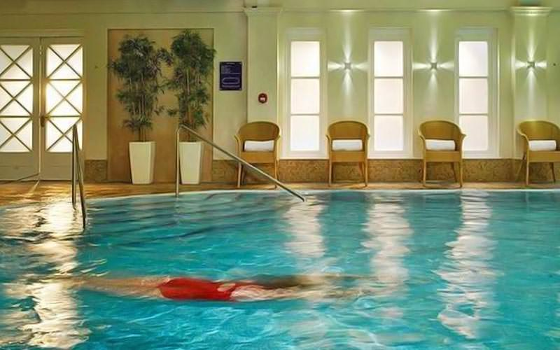 A woman swimming underwater in an indoor swimming pool