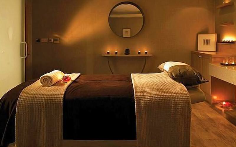 A beauty treatment room with a massage bed in the middle, with lit candles in the background