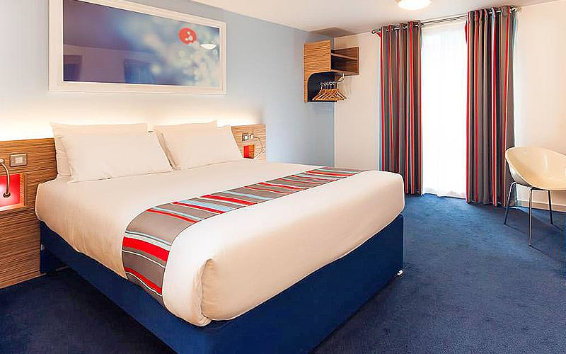 Double bed in a blue hotel room, with a white chair in the corner of the room