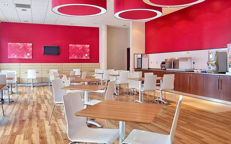 Tables and chairs in a pink hotel restaurant, with breakfast counters on one wall