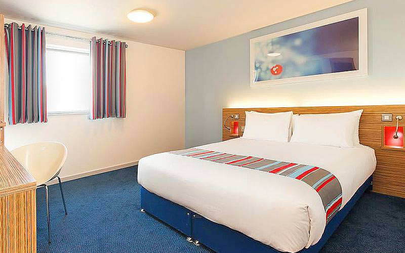 A double bed in a blue hotel room, facing a wooden desk