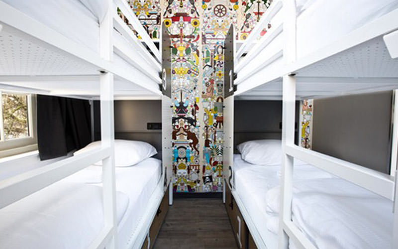 Two white bunk beds on either side of a room, with a colourful mural on the back wall